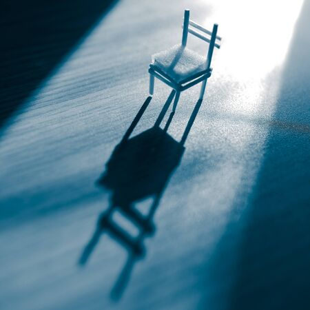 Old chair with a light in the dark blue room