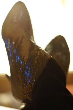 Female legs in sequins shoes on the table