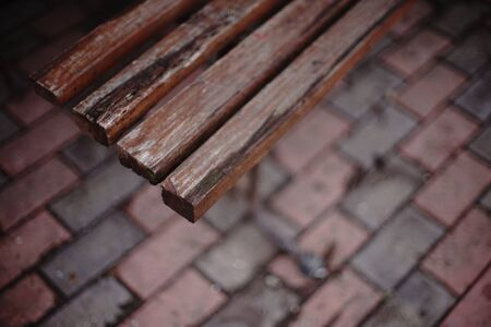Old wooden bench with peeling paint, top view, blurred tiled floor