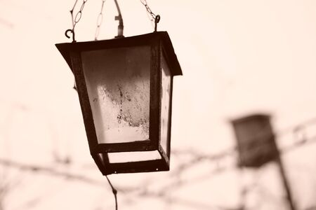 Old retro lantern hanging on a chain in the garden. Sepia photo