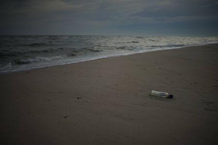 empty glass bottle lies on a sandy sea beach, environmental pollution 스톡 콘텐츠
