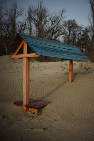 Wooden bench with a canopy covered with sand on a sea beach 스톡 콘텐츠
