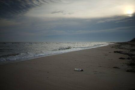 Wild sandy sea beach wirh empty glass bottle on a wet sand