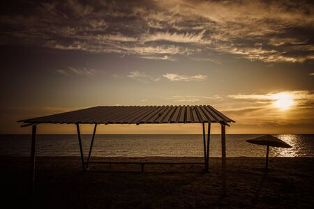 Canopy and old metal umbrella on sandy beach at sunset