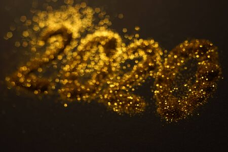 Flickering greeting card with a gold inscription 2020 on a black blurred background