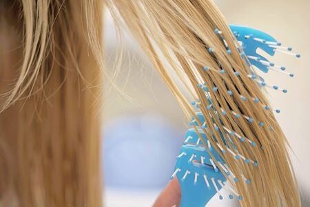 Young girl combing her wet blond hair with a blue comb