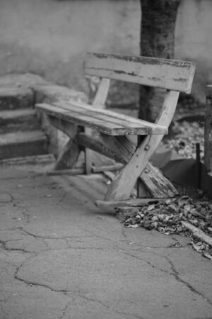 Old wooden bench with peeling paint, bw photo.