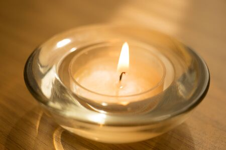low candle burns in a round glass candlestick, closeup