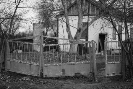 Old rickety fence with open gates in a rural yard