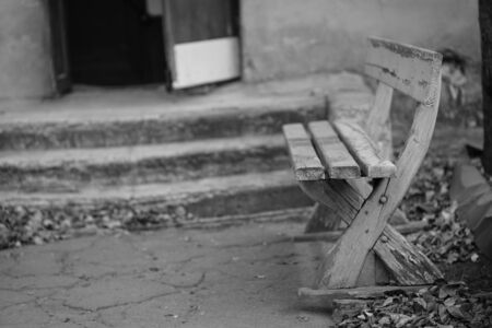 Old wooden bench with peeling paint in old city yard, bw photo Imagens