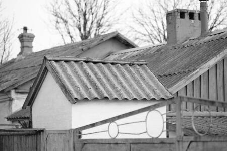 Rural old roofs covered with corrugated asbestos cement sheet, bw photo