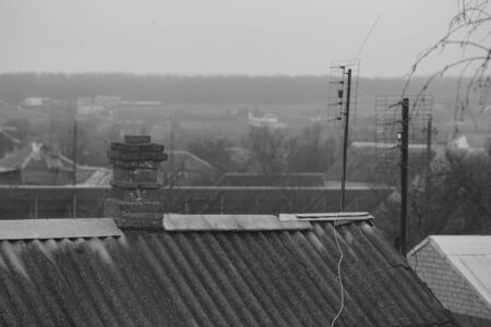 Old rural roof made of corrugated asbestos cement sheet, brick chimney and tv antennas, cloudy day, rural landscape