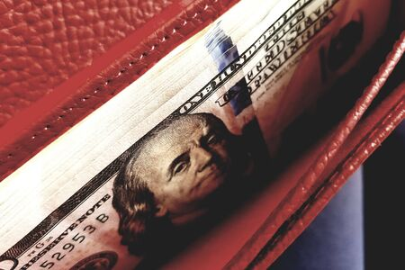 Opened red purse with heap 100 dollar bills closeup
