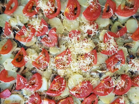 Ready hot food background with slices of tomatoes, potatoes and mushrooms.
