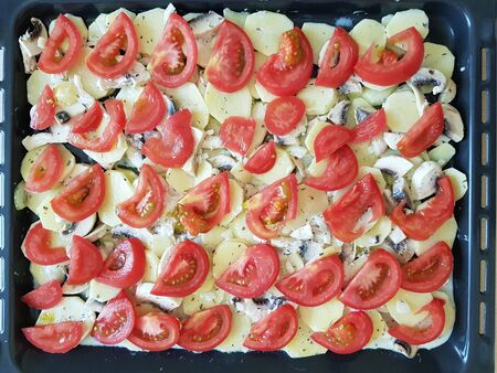 Food background with slices of tomatoes, potatoes and mushrooms in a baking pan in the oven 스톡 콘텐츠