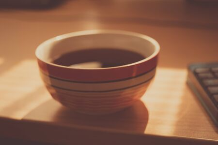 Big round bowl with black tea drink on sunny brown table