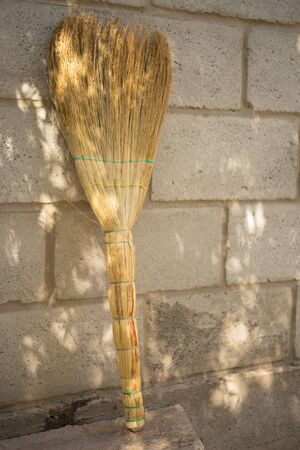 A new wicker broom stands upside down against the stone wall