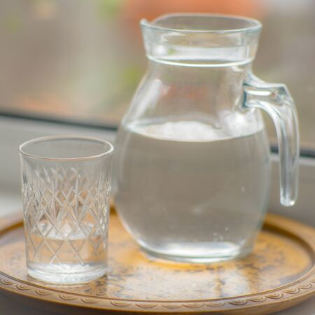 Jug of water and a glass on the windowsill