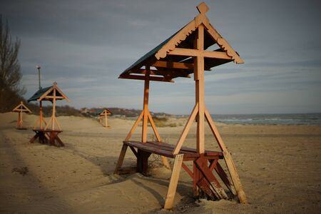 Wooden old bench with a canopy on a sandy sea beach. 스톡 콘텐츠