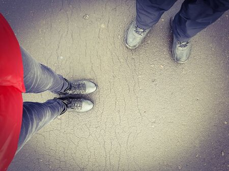 Two people a guy and a girl are standing on the road in leather boots. View from above