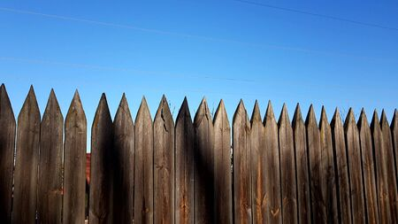 Fence made of sharp wooden stakes, blue clear sky, sunny day