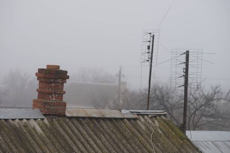 Two antennas and old red brick chimney on the roof, autumn foggy rural landscape