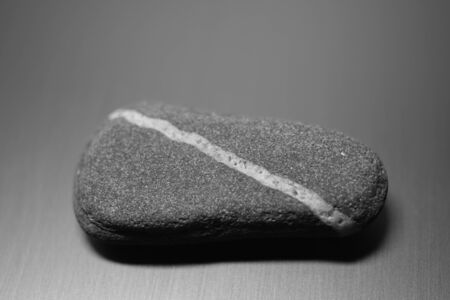 Pebble stone with natural diagonal white line on the table, bw photo Banque d'images - 135481072