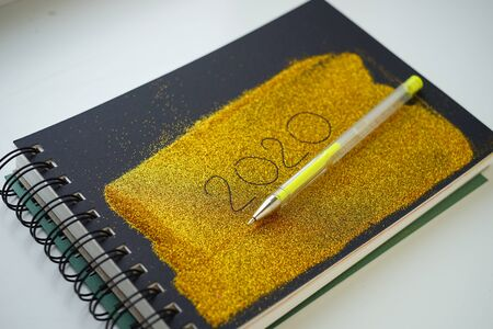 Golden notebook with 2020 inscription, gel pen for new year idea
