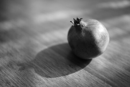 Whole ripe pomegranate on the wooden sunny table, bw photo