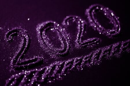 2020 number poured from gold glitters on a dark violet background