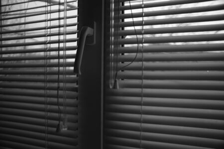 Window with half closed blinds in dark room. Jalousie background. Black and white photo