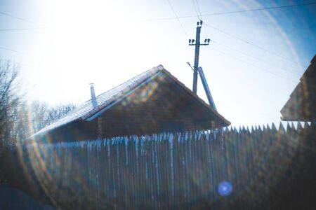 Wooden house with a picket fence and electric pole. Winter sunny day. Beautiful sunbeams around