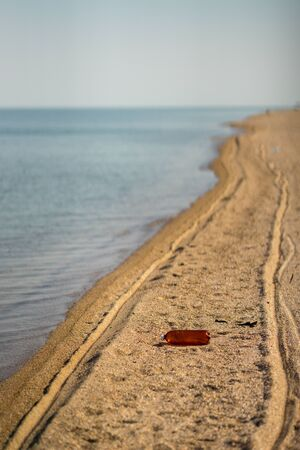 Empty plastic bottle lying on the beach. Environmental pollution. Tire tracks on the sand Stock Photo