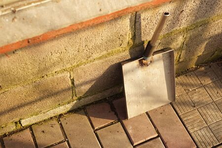 homemade dustpan is standing against the wall of the house on the tiled floor of the courtyard