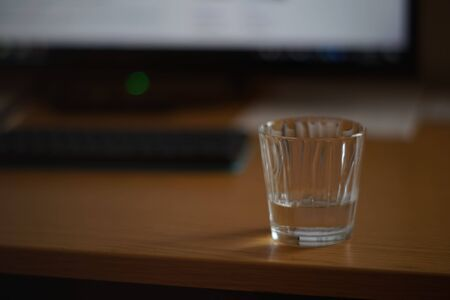 Half a glass of water on a table with a keyboard and monitor in blur