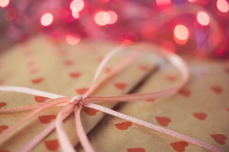 Gift in paper packaging with a pattern of red hearts, ribbon bow and pink lights on background.