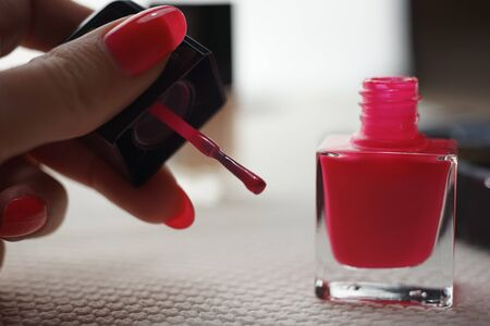 Open glass bottle with a brush and pink nail polish on a white table, female hand in blur.