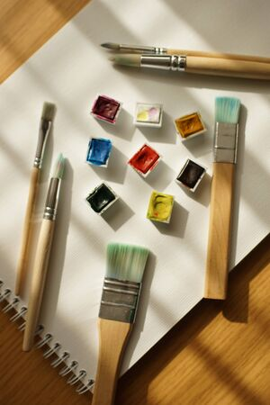 Plastic cells with watercolor paint and various brushes on a white album paper. Art supplies on wooden table