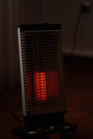Vintage electric heater Ugolek with a burning lamp in dark living room.