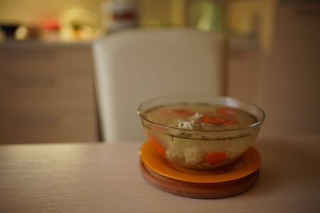 Soup with meatballs in a large glass plate on a wooden table. Kitchen and chair on blurred background