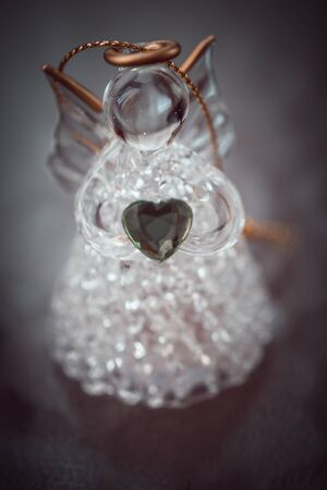 glass angel with heart on the dark brown vignette