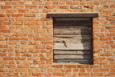 Boarded up with wooden planks window opening in an old red brick wall. Afternoon Lighting