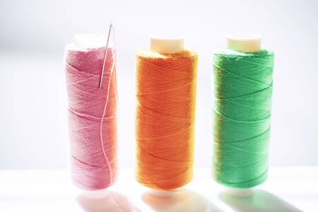 Three spools of thread and a needle on a white bright table, side view.