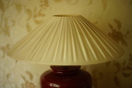 Table lamp with pleated lampshade in a day room, closeup. Standard-Bild