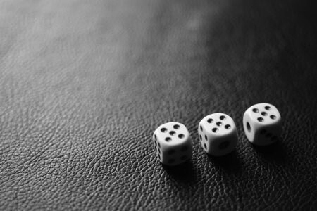 Three dice with fives on a black leather table in corner. Bw photo, 版權商用圖片