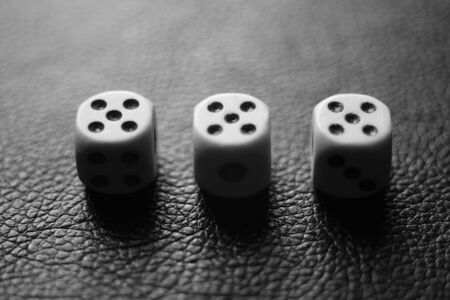 Three dice with fives on a black leather table. Bw photo.