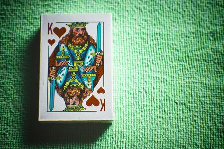 A deck of new cards in a paper box on a green table.