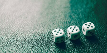 Dice with fives on a green leather table.