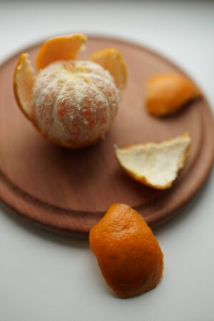 Ripe orange mandarin with peel slices on a wooden board.
