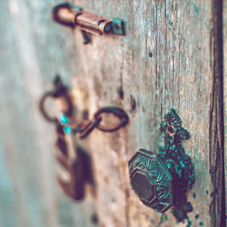 Old wooden door with a vintage handle, hook, lock and mesh. Boho style
